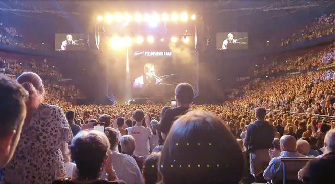 The audience stand from their seats to applaud the singer following the announcement of his donation.