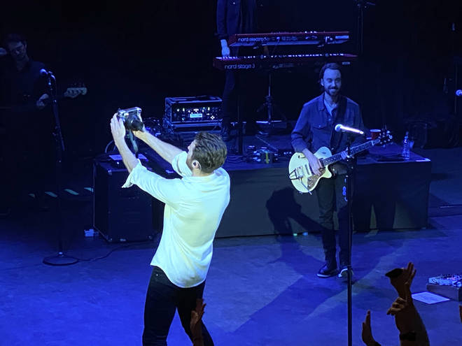 Brett Eldredge taking a photo of the audience in London on his Polaroid camera