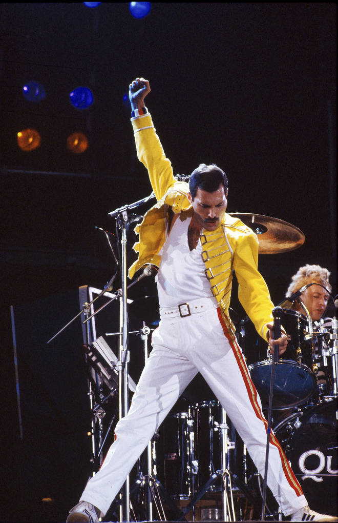 Freddie Mercury performs on stage with drummer Roger Taylor behind on the Magic Tour at Wembley Stadium, London, July 1986