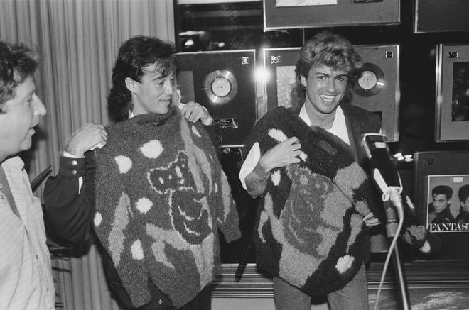 Andrew Ridgeley and George Michael holding koala motif sweaters during the pop duo's 1985 world tour, January 1985. Behind them are awards for record sales, including one for their first album, 'Fantastic'.