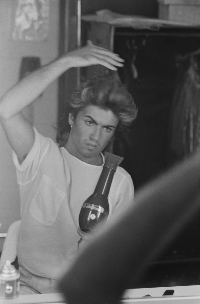 George Michael blow drying his hair during the pop duo's 1985 world tour, January 1985.