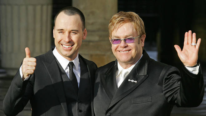 "Sir Elton John (R) and his partner David Furnish pose for photographs at the Guildhall in Windsor, 21 December 2005, after conducting a short civil ""wedding"" ceremony at the registry office"
