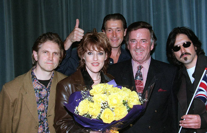 Terry Wogan helps Katrina and the Waves Kimberley Rew (far left), Alex Cooper (blue shirt) Katrina (holding flowers) and Vince de la Cruz (far right) celebrate at Heathrow Airport