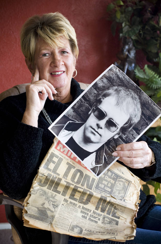 Elton John's ex-fiancé Linda Hannon holding a newspaper and photo of the singer in 2010