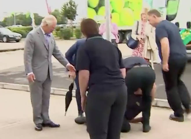 Members of staff rushed to help the man as Prince Charles waited to see if he was ok