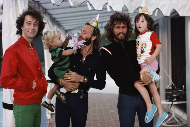 Bee Gees (left to right) Robin, Maurice and Barry Gibb with their children in Miami, Florida, March 1978.
