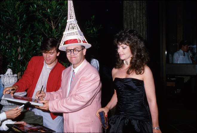 Sir Elton John wears an Eiffel Tower hat as he signs an autograph while his now ex-wife Renate Blauel looks on