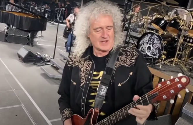 """The footage shows Adam, Brian, Roger and their keyboardist Philip """"Spike"""" Edney play a rousing rendition of &squot;Hammer To Fall&squot; to the vast arena as they dance and joke around with one another."""