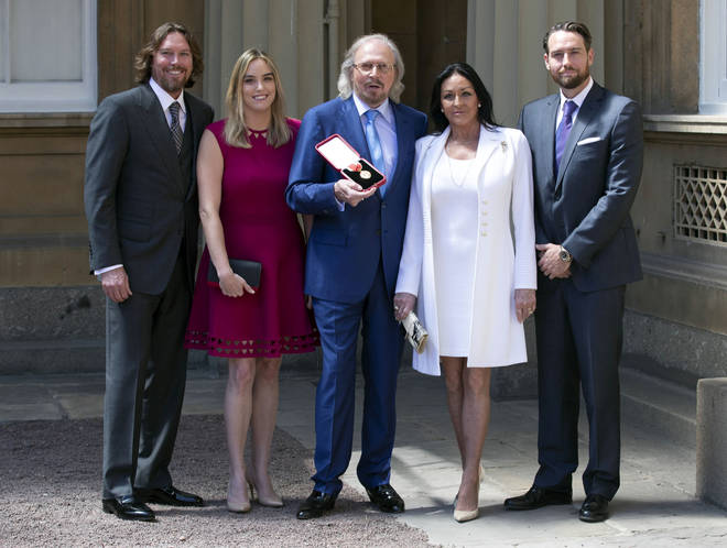 Barry Gibb, with his wife, Linda and children, Michael (right), Alexandra and Ashley (left) at Buckingham Palace, London, after he was knighted by the Prince of Wales during investitures at Buckingham Palace on June 26, 2018