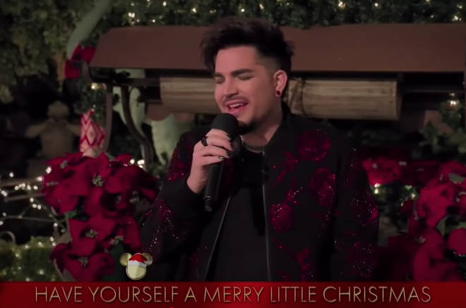 The Queen frontman was filmed sitting on a red brick wall, surrounded by festive red poinsettia flowers and fairy lights