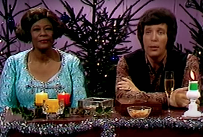 The pair are seen on the video sitting in front of a live studio audience in front of a banquet table filled with christmas accessories and surrounded by christmas trees and fairy lights.