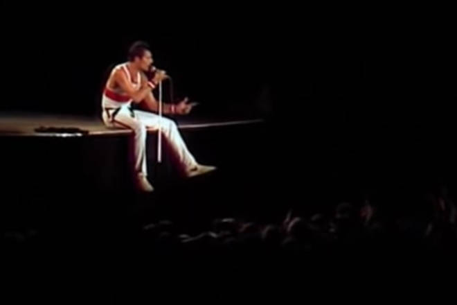 """Freddie Mercury proclaimed to the crowd that he felt """"positively knackered"""" and proceeded to sit on the edge of the stage"""