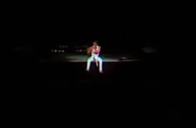 The camera then pans to an image of a tiny Freddie Mercury, feet dangling over the edge of the stage and surrounded by darkness, with only the sounds of an invisible roaring crowd singing every note back to him for company.