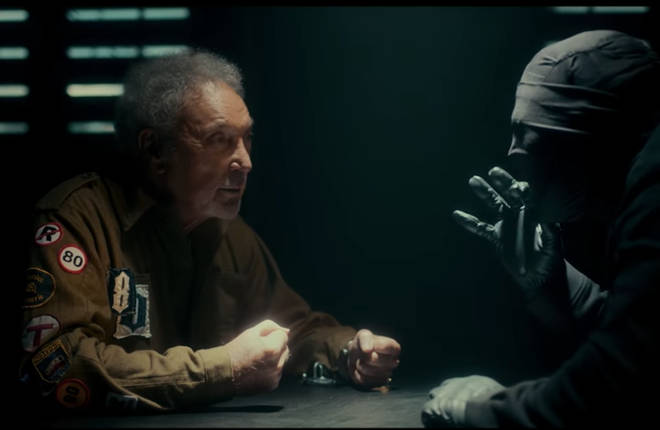 Accompanying the new single is a fantastic music video that sees the star being interrogated by a masked man as they both sit in a darkened interview room.