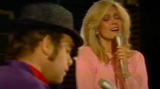 Elton John appeared on TV special Olivia Newton-John: Hollywood Nights when she invited him to come on stage and play a special version of his 1973 hit, 'Candle In The Wind.'
