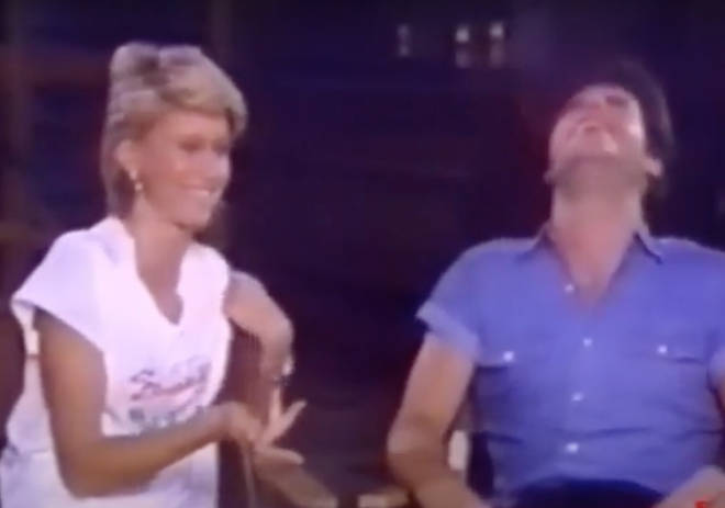 "Olivia Newton-John gestures to a laughing Travolta and says to the camera, ""This is a typical day..."""