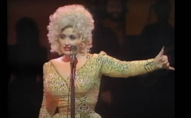 Dolly Parton doing an impression of Elvis Presley is the best thing we've seen in ages. Pictured in London in 1983.