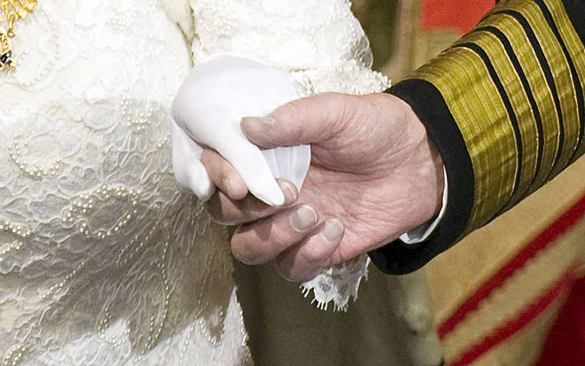 Prince Philip holds the hand of his wife Queen Elizabeth as they attend the State Opening of Parliament on December 3, 2008.