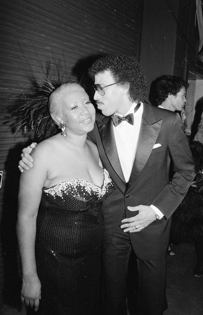 Lionel Richie kisses Aretha Franklin on the cheek at the 1985 American Music Awards.