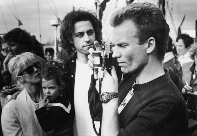 Sting takes a picture at the Sport Aid charity run, London, May 25 1986. Behind him, the event's organizer, Bob Geldof (centre) can be seen with his girlfriend Paula Yates (left)