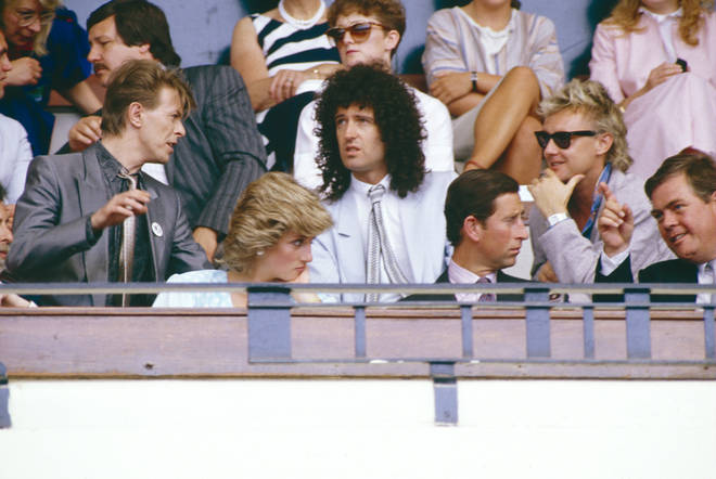 (Back: L to R) Davie Bowie, Brian May and Roger Taylor have a talk during the Live Aid Concert at Wembley Stadium as they sit behind sit behind Princess Diana and Prince Charles (front) on 13th July 1985.