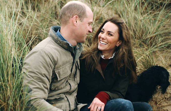 The footage shows the family on a walk on a Norfolk beach and Kate and William laughing and embracing as they sit in the sand dunes (pictured).