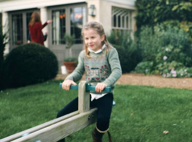 Princess Charlotte can be seen playing on a seesaw with her mother in the background in a still from the video, pictured.