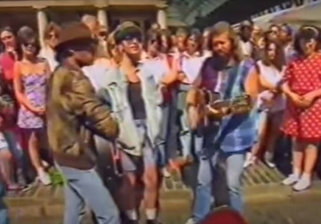 the Bee Gees as they stand in front of an open guitar case and play an acoustic version of their hit songs 'To Love Somebody' and 'Massachusetts' as the crowd stood on all sides watching them sing.