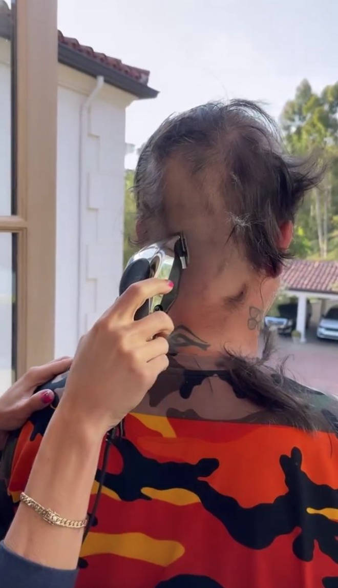 The video then cuts to her gradually slicing away all of his hair and culminates in Robbie Williams' new bald look, reminiscent of the shaved head he sported in the '90s.