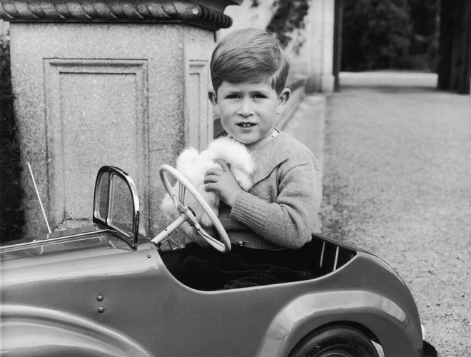 A fresh-faced Charles plays in a toy car in this black and white shot
