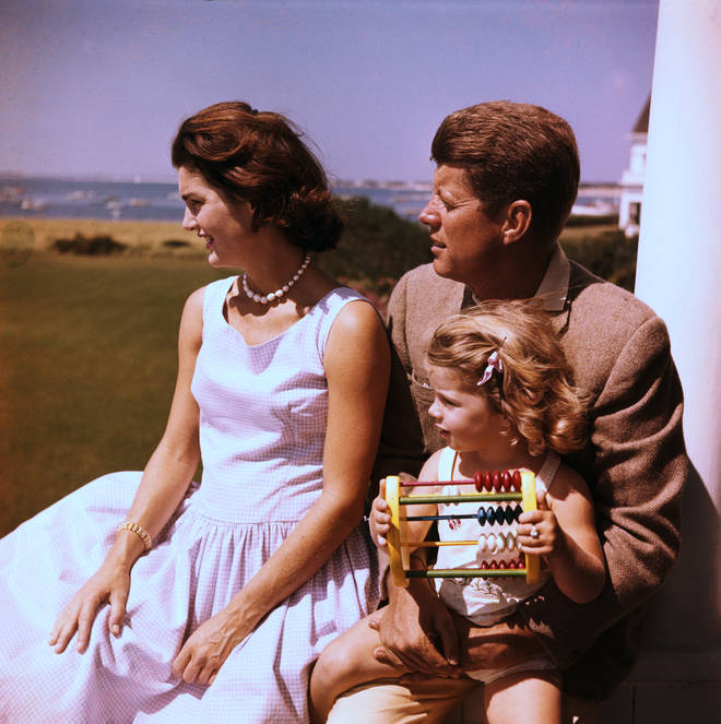 John F. Kennedy relaxes with his wife Jacqueline and daughter Caroline