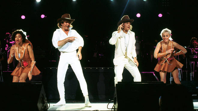 Wham!'s Pepsi, George, Andrew, and Shirlie performing on stage in 1985. (Photo by Michael Putland/Getty Images)