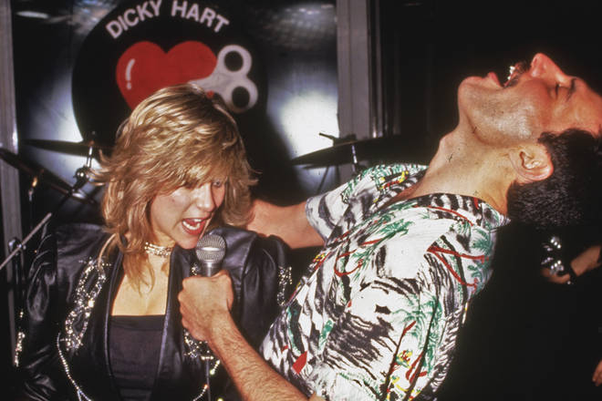 Freddie Mercury performs a duet with Samantha Fox during a party at Kensington Roof Gardens in London, 12th July 1986.