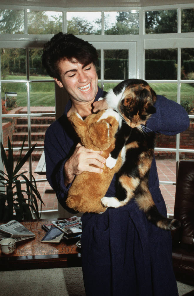 George Michael poses at home with his cat after losing his voice and being forced to cancel a number of live shows in 1980, London.