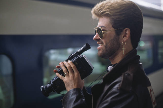 George Michael pictured holding a Sony video recorder device next to a bullet train on a station during the Japanese leg of his Faith World Tour in February 1988.