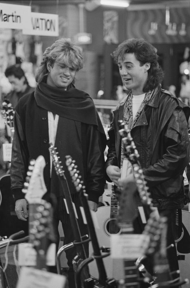 George Michael and Andrew Ridgeley of Wham! looking at a display of guitars for sale, during the pop duo's 1985 world tour, January 1985.