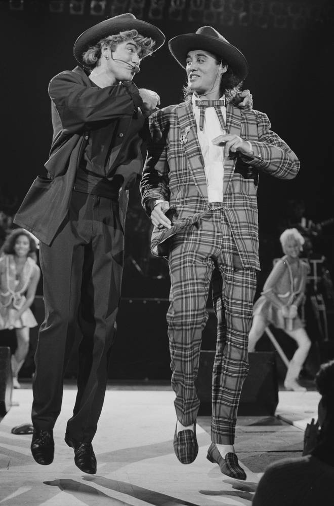 George Michael and Andrew Ridgeley of Wham! performing during the pop duo's 1985 world tour, January 1985. In the background are backing singers Pepsi and Shirley