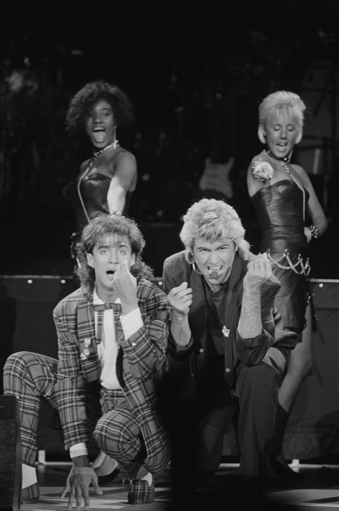 Andrew Ridgeley and George Michael of Wham! performing during the pop duo's 1985 world tour, January 1985. In the background are backing singers Pepsi and Shirley
