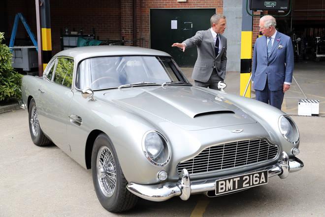 Daniel Craig and Prince Charles inspect the Aston Martin.