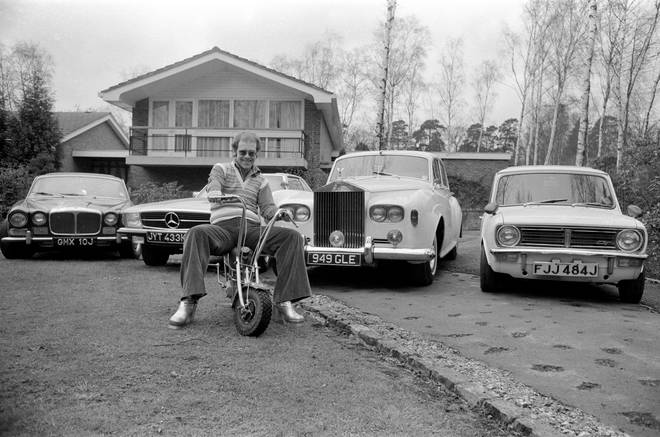 Elton John pictured at his home, sitting on a small motorbike in front of four of his cars. His cars include a Mercedes (2nd left) and a white Rolls Royce (3rd left) Picture taken 4th April 1972.