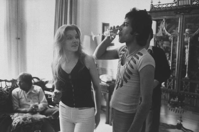 Freddie Mercury (R) drinking a class of champagne as his girlfriend Mary Austin looks on during party for friends at home in 1977
