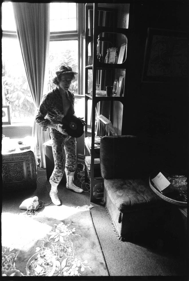 David Bowie holding an LP at his ground floor flat at Haddon Hall, where he has been redecorating the ceiling in silver paint, Beckenham, Kent on 24th April 1972.