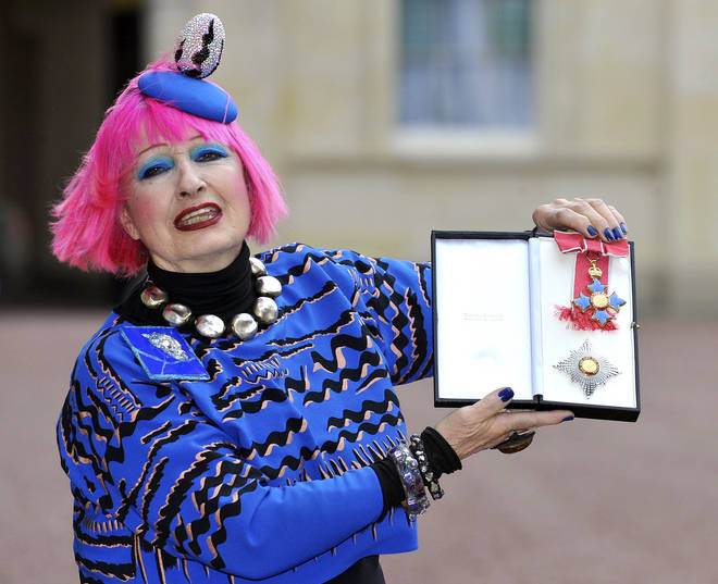 Zandra Rhodes holding her Dame Commander of the Order of the British Empire medal