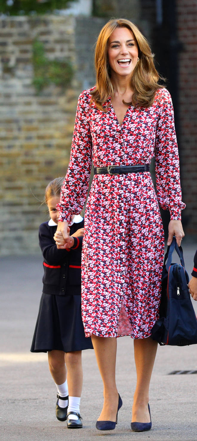 Princess Charlotte hiding behind the Duchess of Cambridge's dress