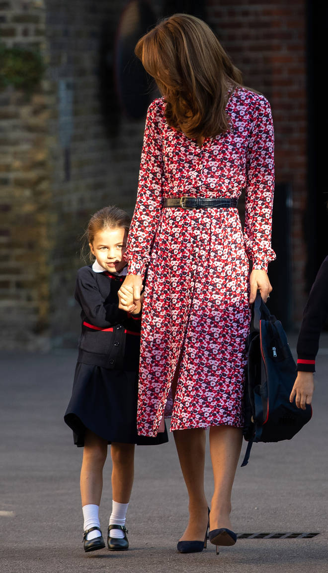 Princess Charlotte hiding behind her mother's dress on the way to school