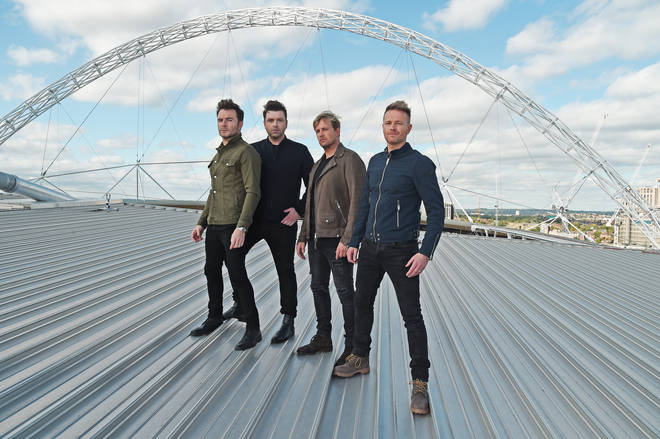 Westlife posing on the roof of Wembley Stadium after speaking to Smooth Radio