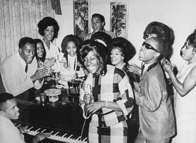 Motown founder Berry Gordy Jr. playing the piano as a group including Smokey Robinson and Stevie Wonder join in singing together at Motown Studios in 1964